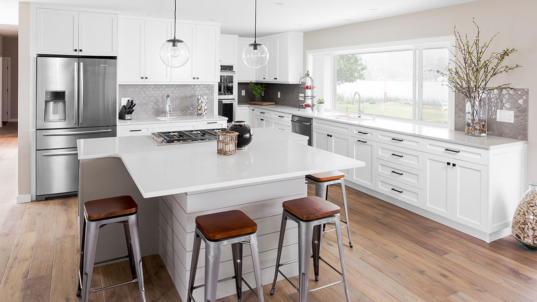 White shaker cabinets, gray island, quartz and wood flooring in a renovated lakefront kitchen.
