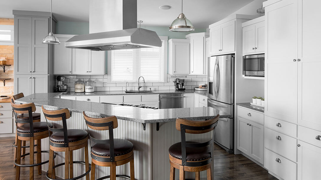 Gray and white shaker kitchen cabinets, custom island, quartz countertops and stainless appliances.