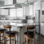 Gray and white shaker kitchen cabinets, custom island, quartz countertops, and stainless appliances.