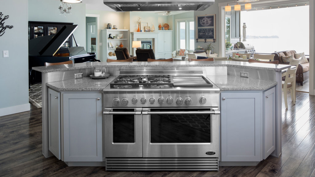 Gray shaker cabinets in a custom kitchen island with stainless steel appliances and granite countertops.