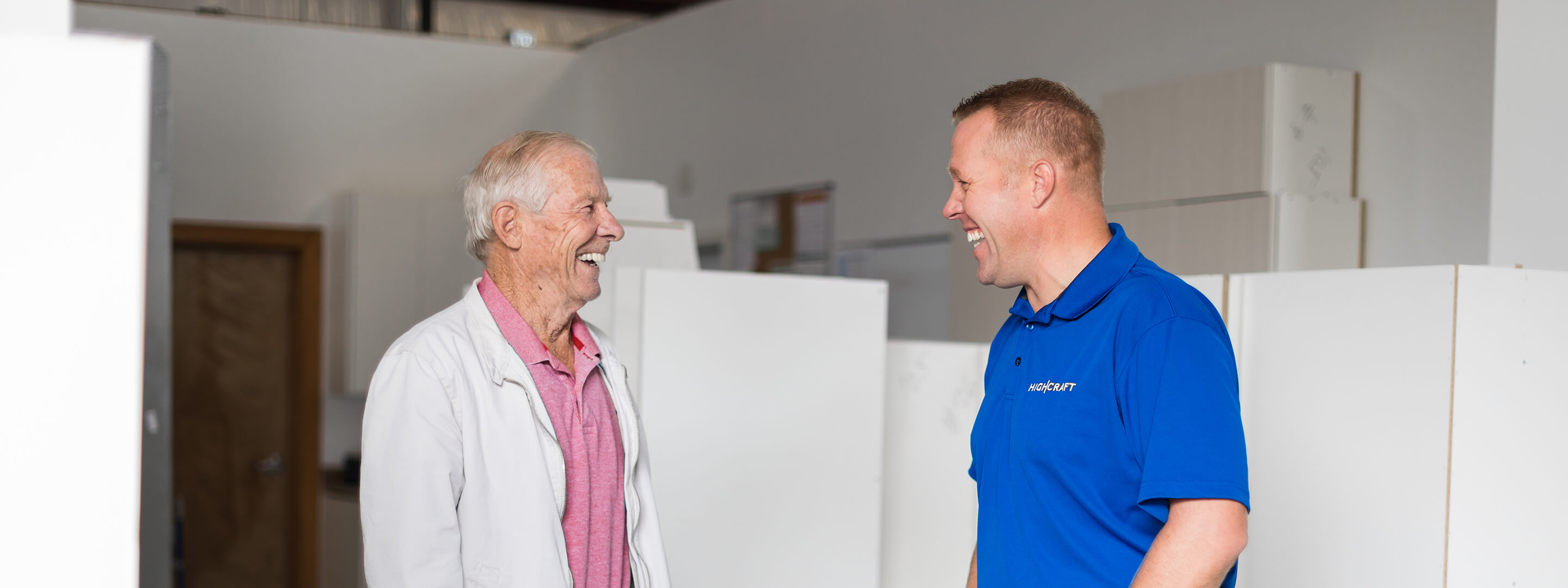 Two men in red and blue shirts smile while talking in a cabinet manufacturing factory.