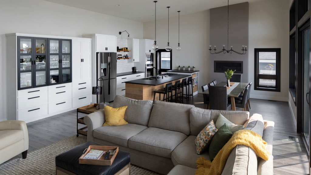 An open concept living room and kitchen with white cabinets, wood flooring and black accents.