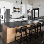 Custom white slab and shaker cabinets in modern kitchen with black granite and wood accents.