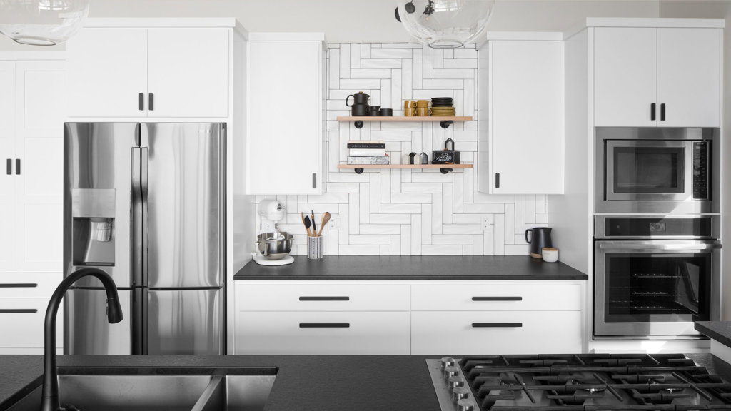 White Euro cabinets in modern kitchen with black granite countertops and stainless steel appliances.