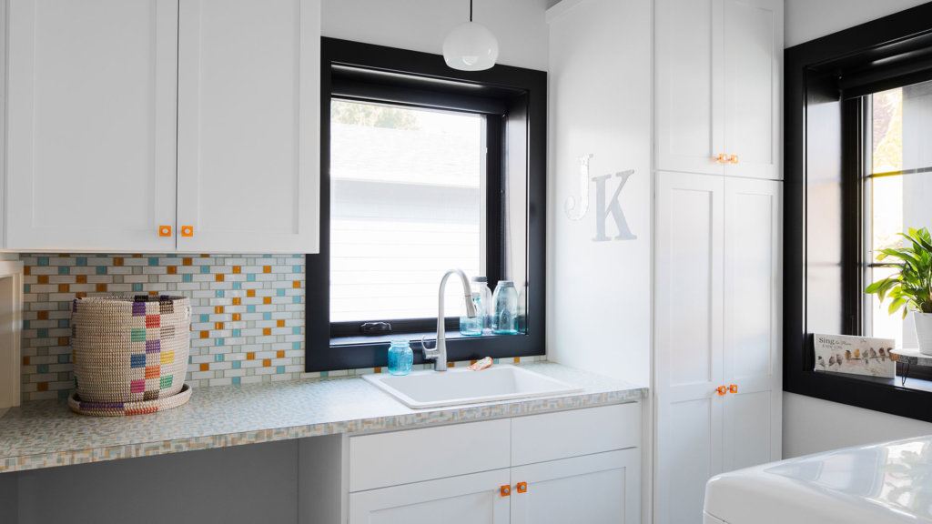 White cabinets, orange knobs, and custom black windows in a bright laundry room.