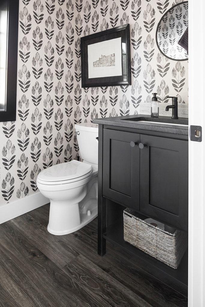 A black bathroom vanity cabinet, patterned wallpaper, toilet and wood flooring in a powder room.