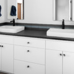 A white European style cabinet vanity with black granite countertops in a master bathroom.