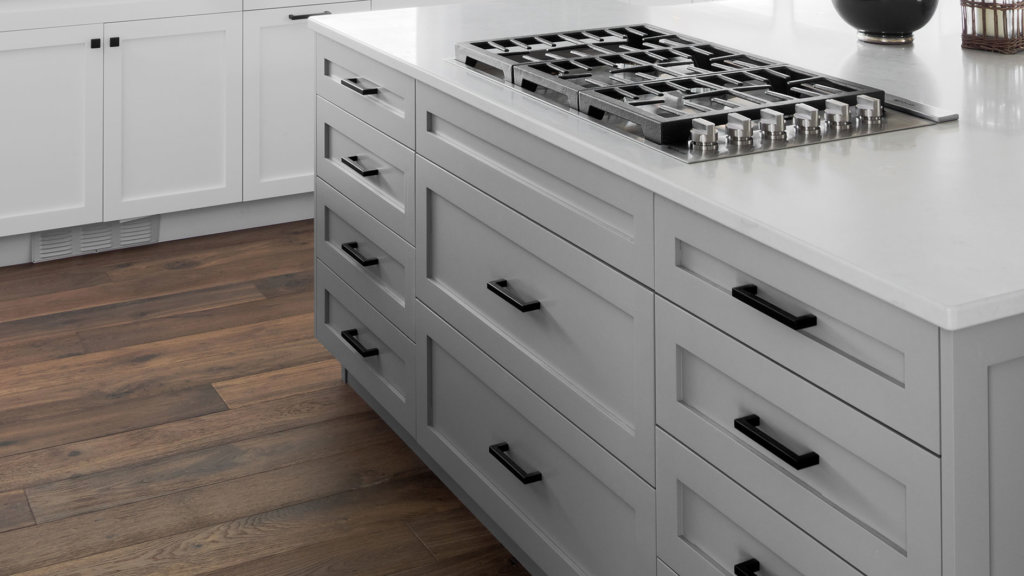 A gray shaker kitchen cabinet island with white quartz countertops and natural wood flooring.