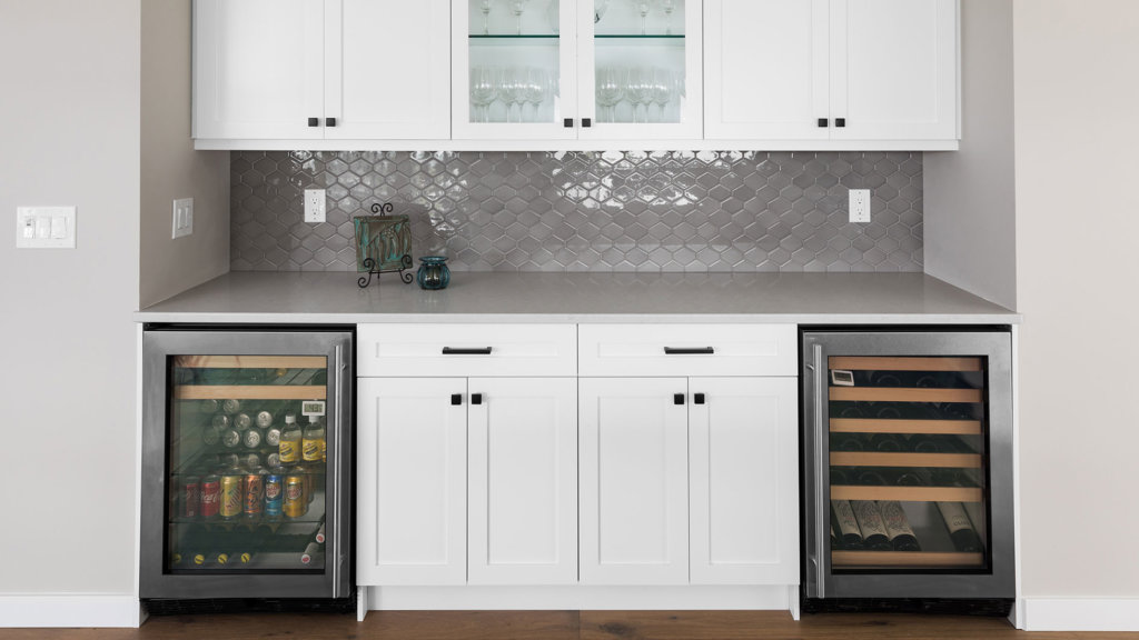 A custom kitchen bar with white shaker cabinets, stainless steel drink storage and quartz countertops.