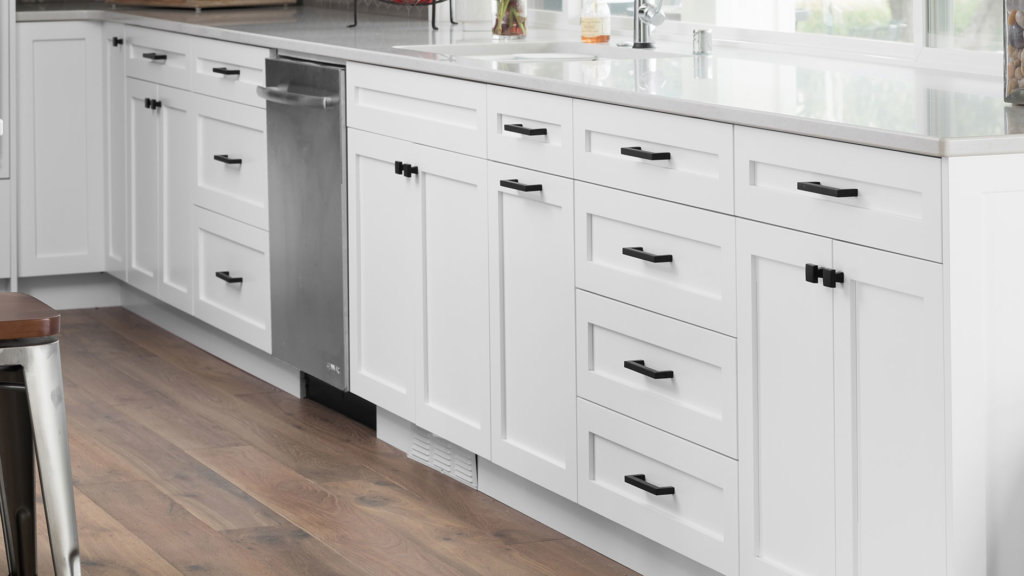 White shaker kitchen cabinets with black square hardware and white quartz countertops.