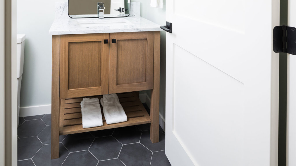 A powder bathroom with gray hexagon floor tile, a wood cabinet vanity and marble countertop.