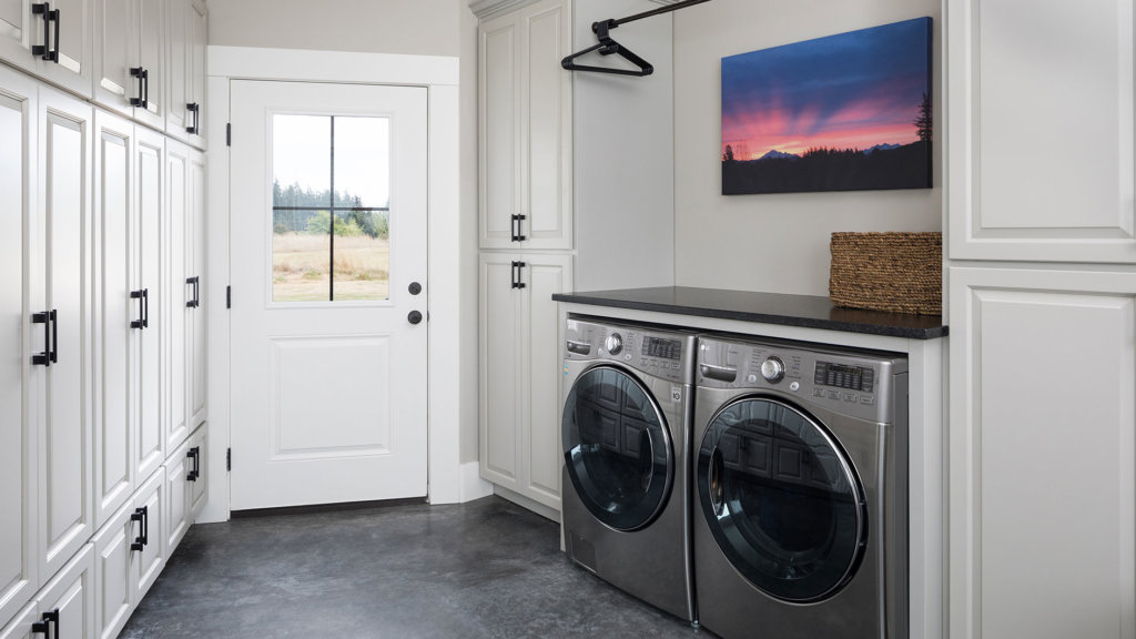 A laundry room with custom white storage cabinets, washer, dryer and a stained concrete floor.