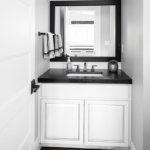 A farmhouse style bathroom with white cabinet vanity, black finishes, and black granite countertop.