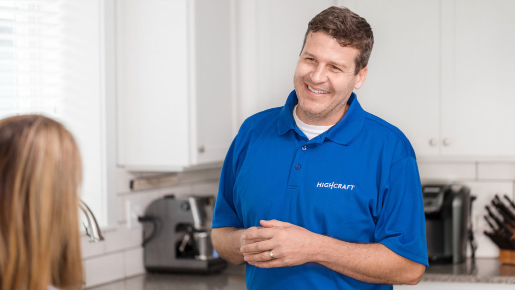 A smiling man in a blue HighCraft shirt talking to a woman in a kitchen.