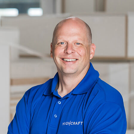 A smiling bald man in a blue HighCraft shirt standing in a cabinet factory.