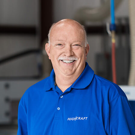 A smiling bald man wearing a blue HighCraft shirt and standing by cabinet manufacturing machinery.