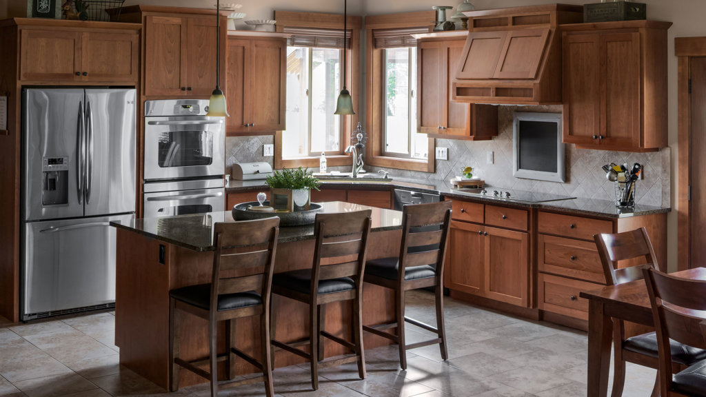 Cherry wood cabinets in a craftsman style kitchen with tile floors and granite countertops.
