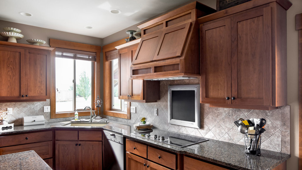 Custom cherry wood cabinets in a craftsman style kitchen with granite countertops and tile backsplash.