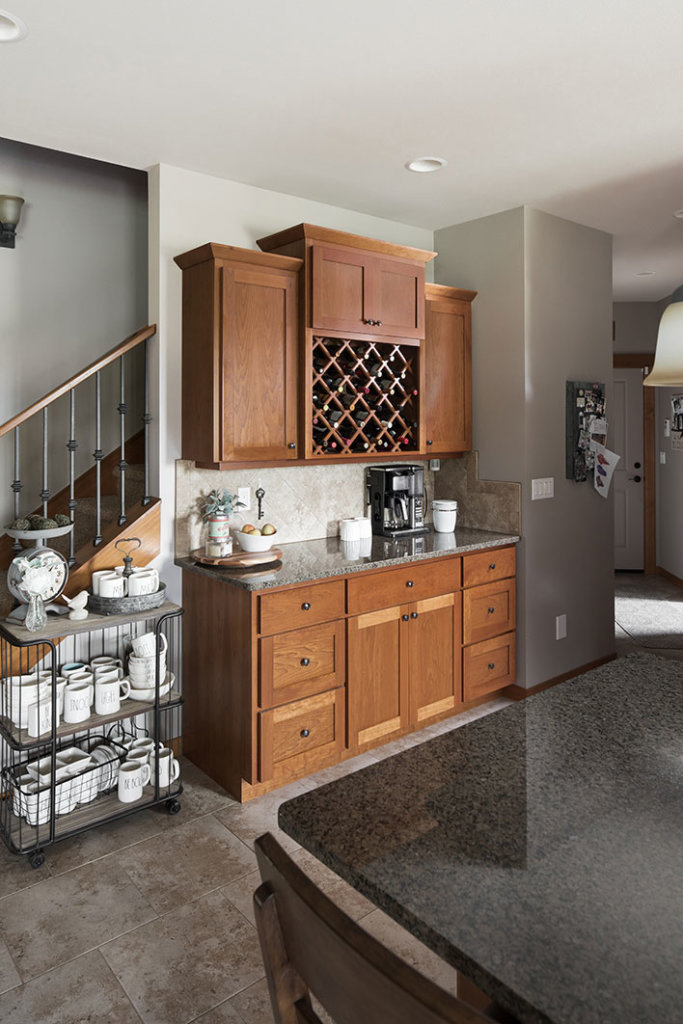 A custom cherry wood wine and coffee bar cabinet in a Pacific Northwest style kitchen.