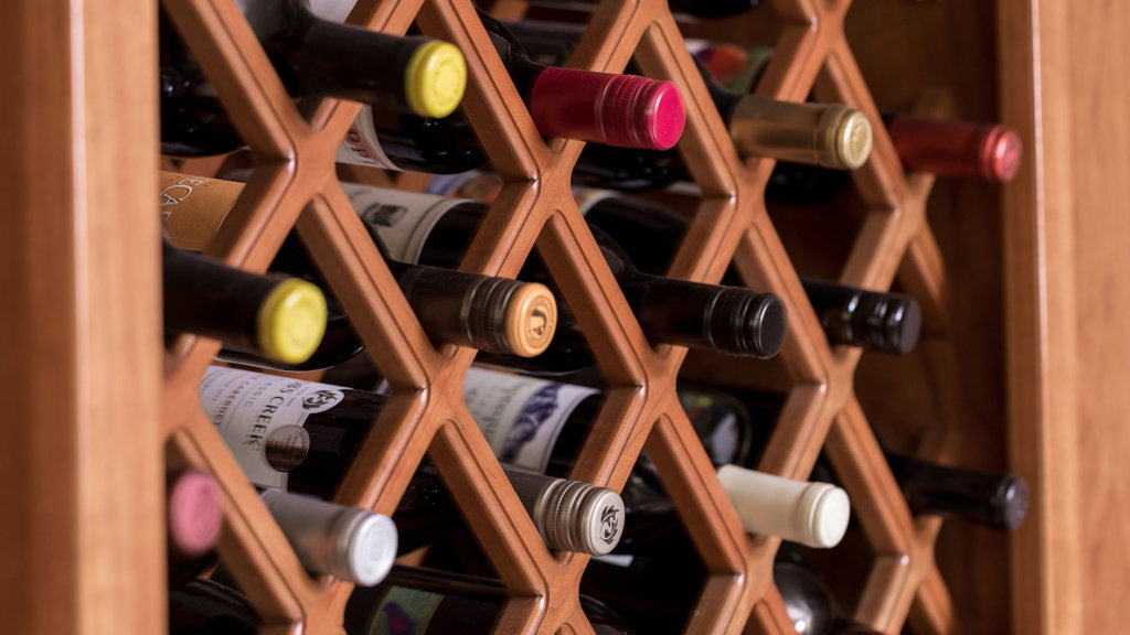A custom wine rack in a cherry wood cabinet holding various bottles of wine.