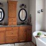 Custom cherry wood cabinets and a white porcelain tub in a craftsman style master bathroom.